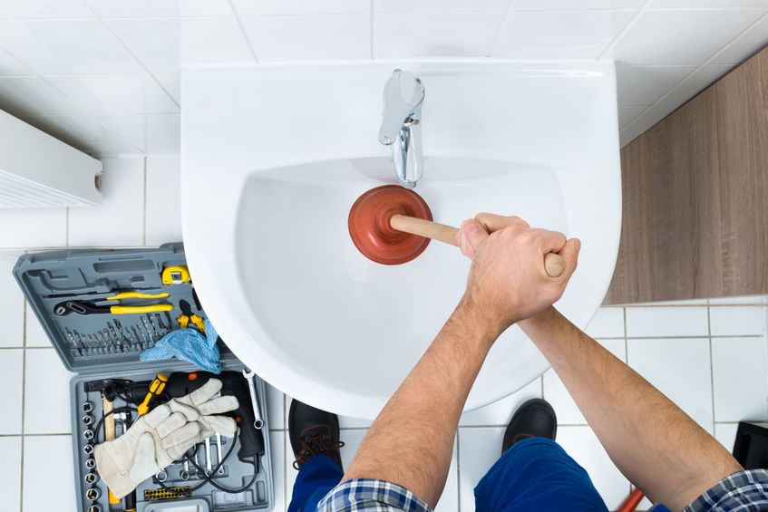 clearing a clogged drain with a plunger