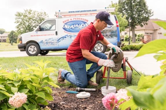 professional sewer technician rodding sewer line